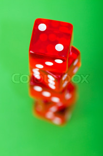 Red dice against green background - shallow DOF