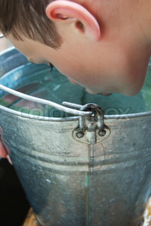 The boy drinking water from a bucket