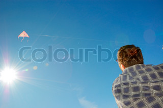 adult man flying a kite against the  blue sky with the sun