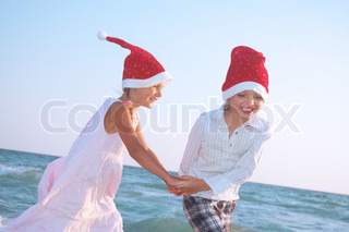 happy 5-6 year old boy and girl with Santa hats dancing on the beach