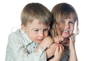 little girl and boy embrace on the white background