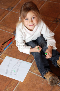 little girl sitting on the floor and drawing a house
