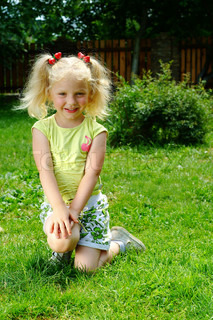 The small blonde with a naughty smile and dimples on cheeks sitting on a green lawn