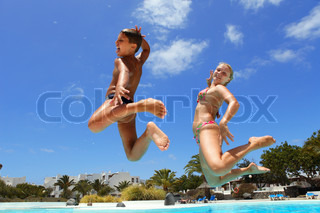 boy  with mum  jumping into the pool smiling