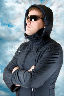 portrat of man in black sunglasses and winter jacket on blue sky background