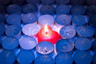 Burning red heart-shaped candle among rows of blown out candles