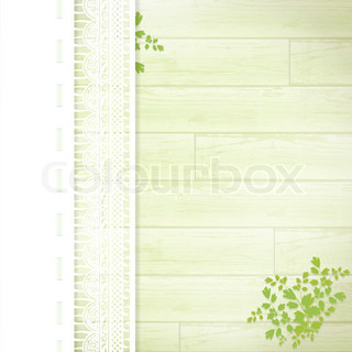 lace frame with green leaves at green wooden background