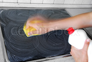 hand with a sponge cleaning surface in kitchen
