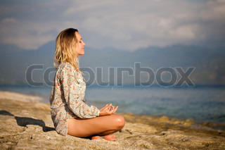 Woman sitting in lotus position on rock by the sea