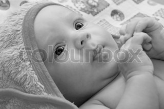 Black and white Portrait of baby boy lying on the bed