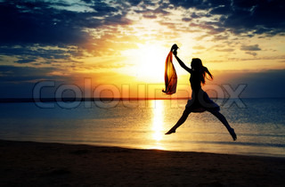 Jumping lady at the summer beach during sunset