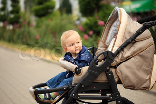 Sweet blonde toddler are sitting in baby carriage outdoor, waiting for mom