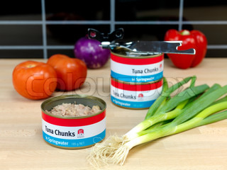 Cans of Tuna isolated on a wooden kitchen bench