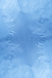 Slightly blurred blue frost pattern on a window glass (with empty space for your text or image)