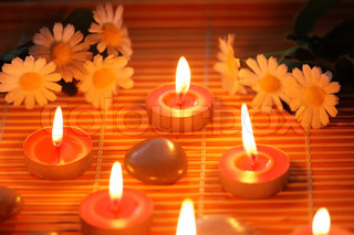 Candles, flowers and pebbles  for aromatherapy treatment