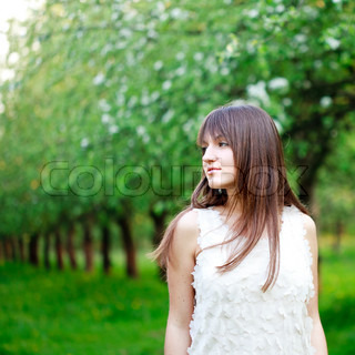 Young attractive girl is walking in the garden