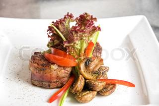 lecker Rindersteak gegrillt in einer gusseisernen Pfanne für gerippte Fry mit Speck, dekoriert mit gerösteten Pilzen und Gemüse