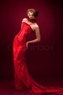 Beautiful girl in red dress over on red background