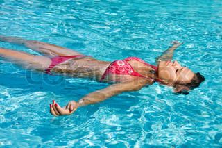 Young girl is swimming in a pool in sunny day