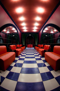 Room with a checkered floor and red sofas