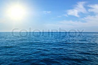 Sea landskab med bjerge og skinnende sol i blå tone