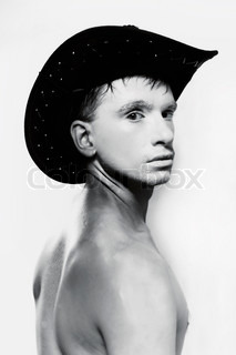 Portrait of young naked man in cowboy hat on white background