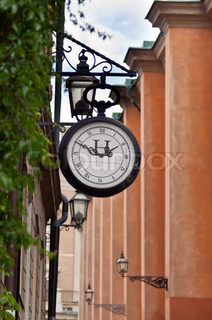 old street clock on the background of a narrow street in Stockholm, Sweden