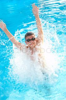 joyful boy in pool. Jump in water