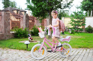 Young school girl with bagpack rides her pink bike to school
