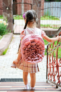 Young school girl with pink bagpack waits standing on stairs