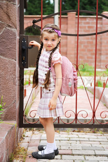 Young school girl in uniform with pink bagpack goes to school