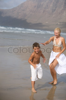 Happy Mother and son play on the beach