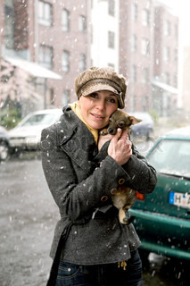woman is holding a little dog outdoors