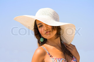 Young beautiful sexy tanned brunette woman with hat and bikini on sea beach