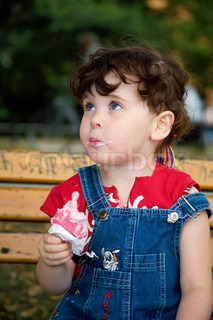 little cute girl is eating strawberry ice-cream