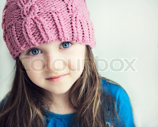Close-up portrait of adorable smiling child girl wearing pink knitted hat