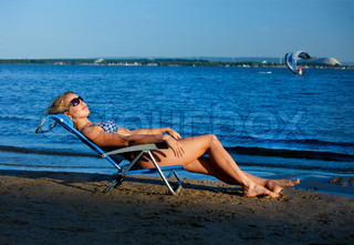girl lying on a beach in a lounge chair