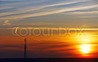 silhouette of mobile phone communication antenna tower on sunset sky background