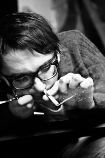 young man in spectacles inhaling cocaine through a straw