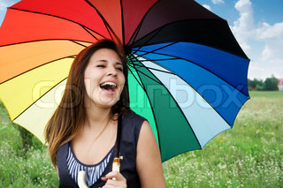 beautiful young girl with a colorful umbrella laughing outdoor