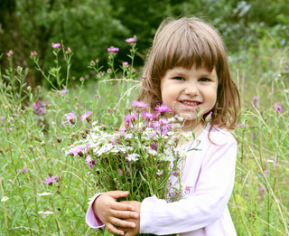Little Smiling Girl with Bunch of Flowers Portrait
