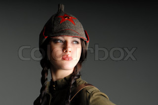 portrait of a young beautiful girl in the  uniform of the red army on dark gray background