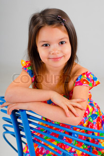 portarit of a cute brown-haired girl wearing bright-colored dress and resting on a fancy chair