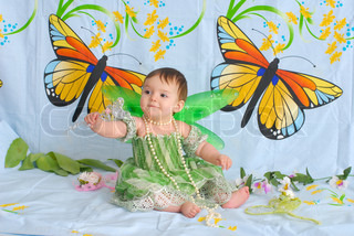 portrait of a sweet smiling baby girl wearing fancy green dress with butterfly wings