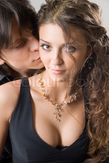 portrait of a beautiful young couple kissing and hugging. Isolated on grey background