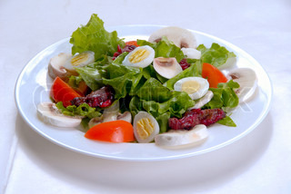 salad of fresh mushrooms, eggs and tomatoes, decorated with leaves of lettuce