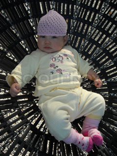 A Baby girl lies in a childrens swing