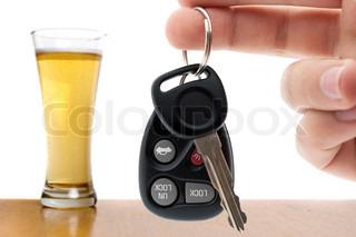 Spirituskørsel konceptuelle billede med en hånd, der holder nogle bilnøgler og et glas øl i baggrunden.
