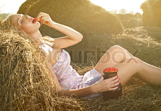 beautiful woman sitting on the hay and eat raspberries
