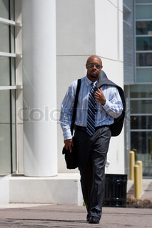A confident business man carries his suit jacket over his shoulder while walking down the sidewalk in the city.